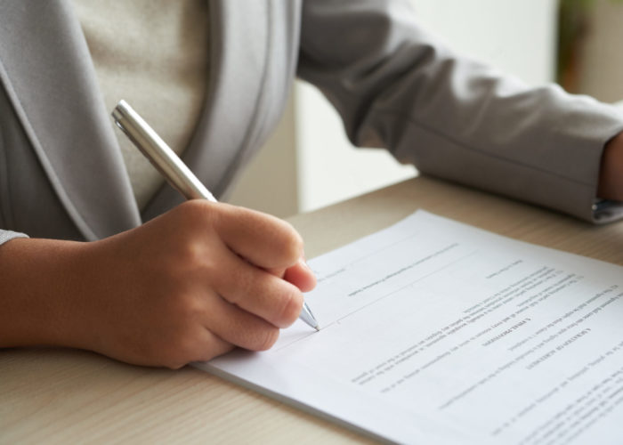 Close-up image of enterrepneur reading agreement before singing it