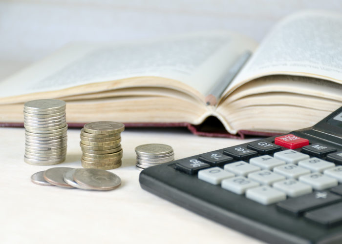 Coins stacked pile, calculator, open book light background. Calculation of financial stability and business development